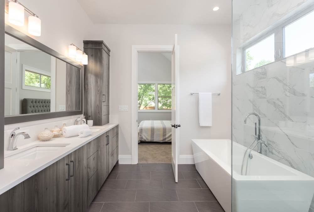 master bathroom interior in luxury home large mirror, shower, and bathtub. Includes dark hardwood cabinets and tile floor. View of bedroom